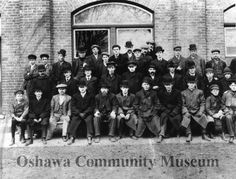 Staff of the Williams Piano Company outside the factory building.  Large group of boys and men.  Black & white matte print mounted to a cardboard backing.