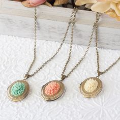 These lovely antique bronze photo lockets have beautiful scalloped lace edge details and feature exquisite resin rose cabochons that come in three beautiful spring colors of ivory, coral peach and mint green. The locket measures approximately 1 1/4 tall x 1 wide and comes on a