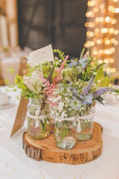 Rustic English country garden flowers in jars for the wedding breakfast, backed by fairy lights. Photo by Sam & Louise • http://samandlouise.co.uk
