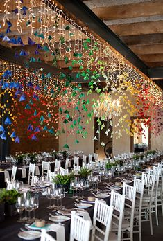 Wedding Decorations 458311699552486961 - Here, ceilings dripping with felt flowers spanning the spectrum of colors offer a festive touch. (Take note: White chairs and relatively sedate table decor help avoid rainbow overkill. Garland Wedding, Wedding Reception Decorations, Wedding Table, Table Decorations, Rainbow Wedding Decorations, Decor Wedding, Wedding Lighting, Hanging Decorations, Barn Lighting