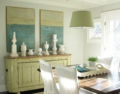 Molly Frey used this antiqued green piece to add a subtle punch of color to this sun washed dining room and pick up the color from lamp shade and art work