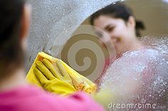 A woman cleaning a mirror wearing rubber gloves.