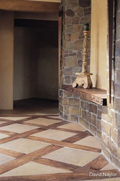 In this basket-weave, wood-and-stone inlay floor, the wood was hand-scraped and pigmented to look like it had been there for hundreds of years.: