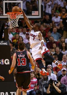 Dwyane Wade #3 of the Miami Heat dunks over Joakim Noah #13 of the Chicago Bulls during a game at American Airlines Arena on January 4, 2013 in Miami, Florida.