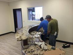 Copenhagen granite front desk being installed at our Springdale location