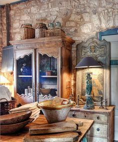 kitchen poetic wanderlust-  Stone..walls, flooring or fireplace adds luscious texture and warmth to any kitchen. Layer in an antique armoire for storage/petite pantry, lamps and mirrors to make the kitchen feel more connected to the house. Wicker and wood...yes, always...keep your eyes peeled! tracy porter
