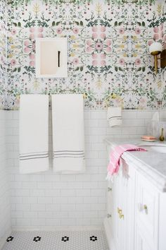 Bathroom Reveal! Check out this beautiful DIY bathroom with pink floral wallpaper, brass accents, a round mirror, marble vanity, subway tiles. It's a girly decor dream! For a small bathroom it sure is big on style!