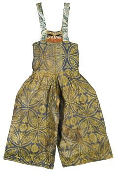 A PAIR OF BLUE SILK TROUSERS, CENTRAL ASIA, 11TH/12TH CENTURY the wide trousers with rectangular top, the shoulder straps and frontal design composed of assorted silk cloths with varying designs and a row of small conch shells, green and white calligraphy on the straps, the central silk garment with yellow geometric foliate designs against a purple ground, top tied at reverse  125cm. length.