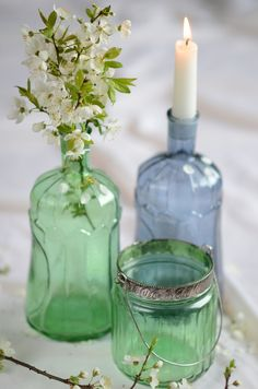 Green glass with white flowers. A blue bottle with a candle. Nice combination.