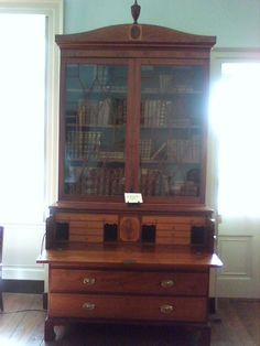 Early 1800's - Book case with glass doors encased in wood with a fold-out writing desk and drawers.
