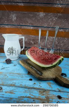 Watermelon with forks ready for eating on garden table - stock photo
