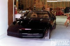 In a never-before-published photograph, one of the original three K.I.T.T. Trans Ams emerges from Jon Ward's shop following completion of exterior modifications. Custom work was done away from Universal Studio's lot to avoid the higher cost of union labor. The iconic red light in the nose was a source of constant frustration since it frequently failed to work, a result of being an eight-segment light that was jury-rigged to operate on a standard ten-segment sweep circuit. After…