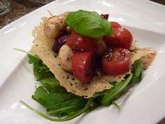 Eine leichte Vorspeise, die fast jedem schmeckt. Der krosse Parmesan, dazu Tomaten-Mozzarellasalat auf einem Beet aus Rucola. Ein paar Antipasti dazu und s