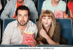 stock photo : Couple with popcorn bag staring ahead in a theater