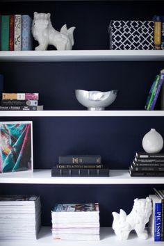 White shelves and accessories against dark blue walls