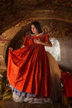 costumefilms:  Mirror Mirror - Lily Collins as Snow White, posing with a red silk dress with gold arabesque embroideries. The bodice is embellished by blue bows; the underskirt is made of lavender taffeta. The costumes were designed by Eiko Ishioka.