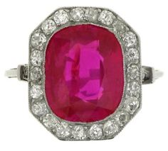 Natural Burmese ruby and diamond cluster ring, French, circa 1910. A platinum ring set with one central oval old cut unheated Burmese ruby in a millegrain collet setting with an approximate weight of 5.94 carats, encircled by a single row of twenty two round old cut diamonds in millegrain bead settings with an approximate total weight of 1.00 carats, above an ornate openwork arcaded gallery, flanked by raised shoulders set with six round rose cut diamonds in bead settings. Berganza.
