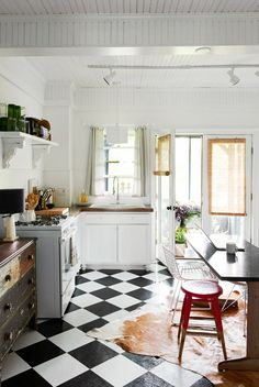 All white kitchen with vintage touches including retro black and white checkered flooring, and distressed wooden cabinets and shelving.