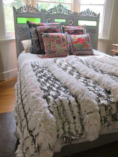 Hmong embroidered pillows, a moroccan wedding blanket as a bedspread and an antique screen as a headboard... great mix of styles and textures in this bedroom.