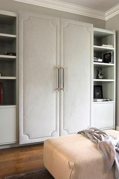Walk-in closet features a wall lined with cabinet fitted with gray fabric paneled doors with silver nailhead trim flanked by gray shelves and cabinets.
