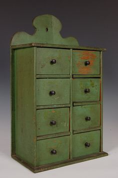 C. 1900 EIGHT DRAWER SPICE BOX IN NICE OLD GREEN PAINTNeat old green surface, scalloped design back, Ash primary wood. Measures approximately 17 h x 10 w x 5.25 d inches.