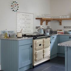 Kitchens: Vintage Kitchen with Blue Cabinets also Cream Aga Stove plus Open Shelving and Graphic Tile Backsplash
