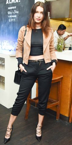 At the Saved Alma event, Bella Hadid topped off her black cropped separates (a midriff-baring top and trousers) with a suede moto jacket, a structured cross-body, and lace-up pumps.