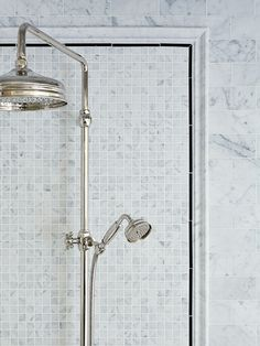 An inset of marble mosaic tile framed with black pencil tile and a marble border highlight the vintage-style exposed-riser shower fittings.