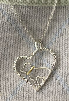Honor the pup who belongs to your heart with our awe inspiring pendant. Handmade in Bolivia, the sterling pendant frames a brass collared pup silhouette within a heart textured to give a crystal-like shining effect.