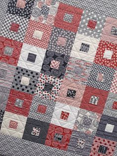 Various shades of reds, grey and black combine to make this cute quilt with gathered centers.