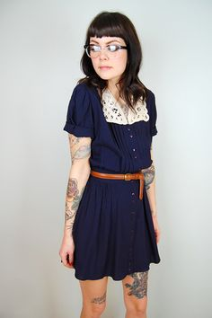 Prettiest simple navy blue dress, skinny brown leather belt, white collar and glasses on a pretty tattooed girl.