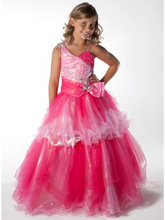 This long pageant dress by Unique Fashion Pageant Gown UF1049F displays one shoulder with beaded spaghetti strap, two tone beautiful beaded bodice with a brooch at the shoulder and the waistline. A full tiered skirt completes this look. Make this lovely dress perfect for your special day.