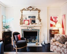 Living Room Red Photo - An antique gold mirror above a marble mantel surrounded by contemporary art