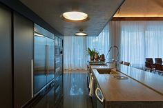Preciosa cocina moderna con comedor y grandes ventanales vestidos con cortinas