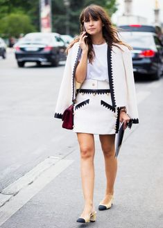 Miroslava Duma wears a white skirt suit with black trim, a burgundy Chanel bag, and Chanel slingback heels