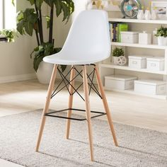 Brighten up the seating arrangement in any room with the white plastic seat of the Baxton Studio modern shell stool. The stool features a retro design with wooden legs, steel hardware and an ergonomic