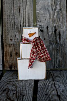 Wooden block snowman -- Cute -- 8 inches tall at Etsy.  I think it would be cute made out of old boxes/crates and made larger for a porch decoration as well.