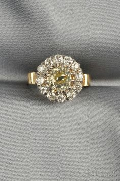 FINE JEWELRY - SALE 2624B - LOT 400 - 18KT GOLD AND DIAMOND RING, SET WITH AN OLD MINE-CUT DIAMOND WEIGHING APPROX. 0.98 CTS., FRAMED BY THIRTEEN OLD MINE-CUT DIAMONDS, APPR - Skinner Inc