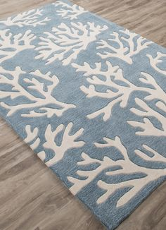 A soft beige coral design against an Arctic Aqua Blue background offers an updated, luxurious beach house theme in this new coastal style area rug.