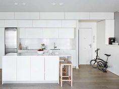 Al usar muebles blancos y sin tiradores, esta cocina se integra perfectamente con la pared. - Copyright © 2017 Hearst Magazines, S.L.