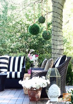 Classic black and white cabana striped cushions add a graphic pop to an outdoor patio.