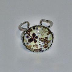 Silberfarbene Metall-Fingerring mit Glas Cabochon Ø 18 mm. Der Ring ist in der Größe verstellbar. Untergrund des Glases ist eine helles Gelb die mit Schmetterlinge versehen sind. Nickelfrei. Hand made. --------------------------------------------------------------------------------- Bitte Lieferzeit beachten! Wird erst bei der Bestellung gefertigt, daher längere Lieferzeit! ---------------------------------------------------------------------------------