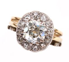 Circa 1880's European old mine cut diamond ring with diamond halo. Found in Switzerland.    Silver and gold antique wedding bands still attached to ring, can be removed if desired. Center stone measures approximately 1.5 cts and is surrounded by 12 mine cut diamonds approximately 1 ct in total weight. Size 4.75, can be sized.  Antique Halo Diamond Ring