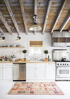 classic white cabinetry, wood (ceiling & countertops), open floating shelves and those factory industrial sconces!!!!