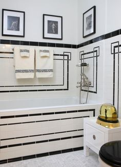 Love the use of black accent tile laid in a graphic pattern in this small white bath