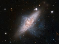 The NASA/ESA Hubble Space Telescope has produced an incredibly detailed image of a pair of overlapping galaxies called NGC 3314 as seen in this spectacular space wallpaper. While the two galaxies look as if they are in the midst of a collision, this is in fact a trick of perspective: the two are in chance alignment from our vantage point.