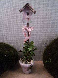Vogelhuisje roze / birdhouse pink. This was made for a dollhouse. There's no reason it can't be made full size for our homes. A flower pot or planter, dowel rod, vines, ribbon and a bird house.