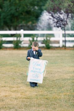 Sign Bearer -- Embarrassed or Sad? Poor little guy! See the wedding on http://www.StyleMePretty.com/2014/04/09/romantic-garden-party-style-wedding/ Photography: BrumleyAndWells.com