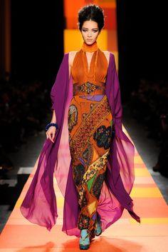 Jean Paul Gaultier Spring 2013 orange dress, halter neckline, fitted waist, diagonal pattern on floor length skirt, purple chiffon shawl, orange bead necklace, ankle bracelet