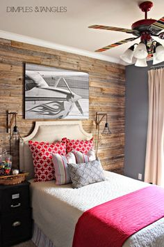 teen boy's bedroom reveal // weathered fence plank wall // DIY // cage sconces // upholstered headboard // airplane art // updated painted striped ceiling fan